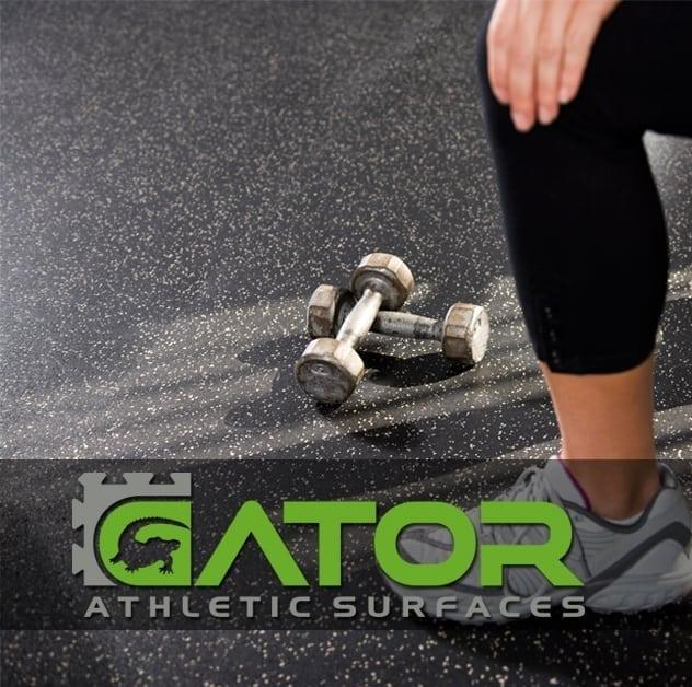 Athlete is kneeling on rubber floor for weight lifting.