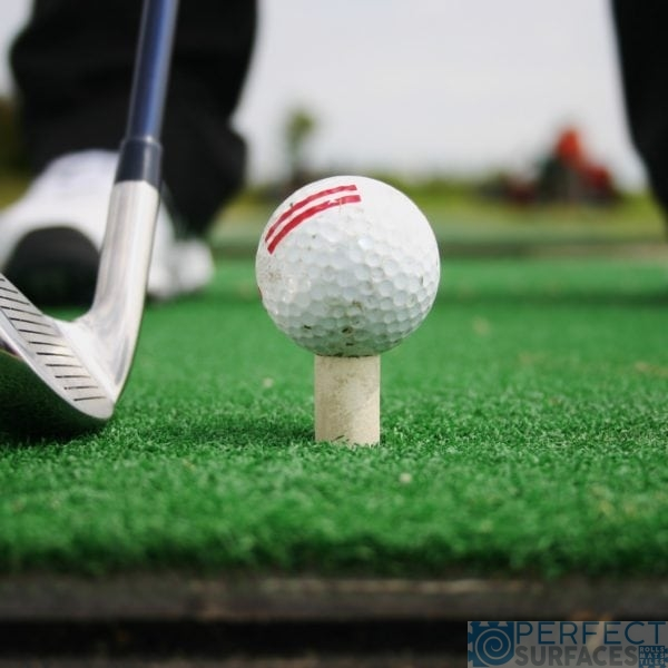 """""""A golfer , preparing himself to shoot the ball on the driving range."""""""
